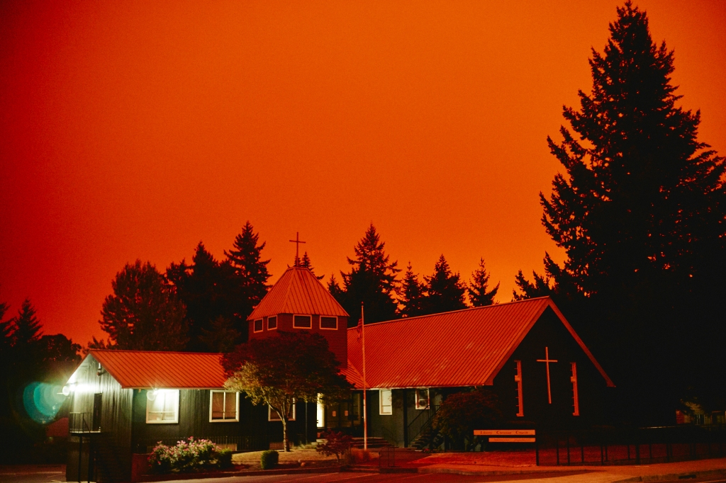 a small dark painted church sits in front of tall douglas fir trees, surrounded by a red sky from the forest fires